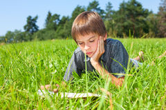 Child reading book outdoor Stock Images