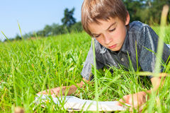 Child reading book outdoor. Boy lying in grass reading a book in a summer field Royalty Free Stock Photography
