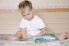 Child reading book on parent's bed Royalty Free Stock Photos
