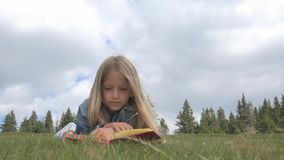Child Reading Book in Park, Kid Student Studying in Nature, Girl Relax Outdoor royalty free stock photography