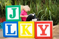 Child reading book in school yard. Kid learning abc letters. Little boy sitting on wooden toy blocks with alphabet in preschool or. Kindergarten. Kids read royalty free stock images