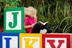 Child reading book in school yard. Kid learning abc letters. Little boy sitting on wooden toy blocks with alphabet in preschool or. Kindergarten. Kids read stock image