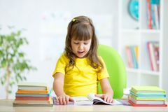 Child reading book at table in nursery Royalty Free Stock Photo