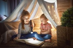 Child is reading a book. Two cute little children are reading a book with flashlights in tent. Happy girls playing at home. Funny lovely kids having fun in room Royalty Free Stock Photography