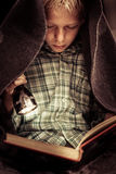 Child reading book under covers with flashlight Stock Images