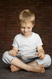 Child reading book. Child in white clothes sitting on floor reading book Stock Image