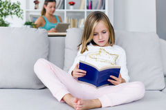 Child reading a book while your mother using digital tablet at h Royalty Free Stock Photos