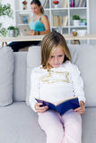 Child reading a book while your mother using digital tablet at h Royalty Free Stock Images