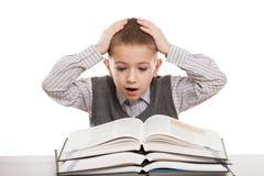Child reading books. Amazed or surprised boy reading education books at desk Royalty Free Stock Image
