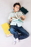 Child reading books on the floor Royalty Free Stock Image