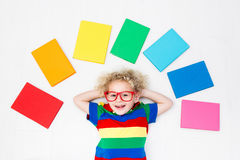 Child reading books. School for kids. Little boy with colorful rainbow books. Happy back to school student. Child reading and doing homework. Preschooler kids Royalty Free Stock Photo