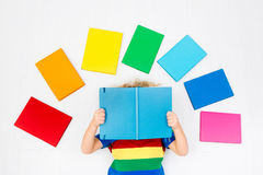 Child reading books. School for kids. Little boy with colorful rainbow books. Happy back to school student. Child reading and doing homework. Preschooler kids Royalty Free Stock Photography