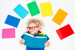 Child reading books. School for kids. Little boy with colorful rainbow books. Happy back to school student. Child reading and doing homework. Preschooler kids Stock Photos