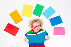 Child reading books. School for kids. Little boy with colorful rainbow books. Happy back to school student. Child reading and doing homework. Preschooler kids Royalty Free Stock Images