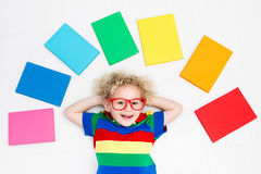 Child reading books. School for kids. Little boy with colorful rainbow books. Happy back to school student. Child reading and doing homework. Preschooler kids Stock Images