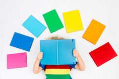 Child reading books. School for kids. Little boy with colorful rainbow books. Happy back to school student. Child reading and doing homework. Preschooler kids Stock Photo