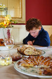 Child reading christmas story. A young boy (6) sitting at the christmas breakfast table and reading the nativity story from the bible, while pointing with his Royalty Free Stock Photo