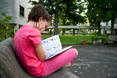Child reading a comic. On a bench Royalty Free Stock Images