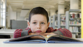 Child reading and daydreaming. Royalty Free Stock Photo