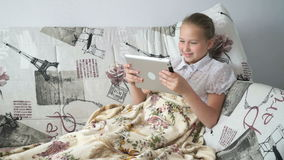 Child reading a digital tablet lying on the bed stock footage