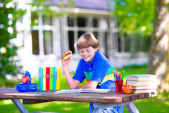 Child reading and eating sandwich at school yard Royalty Free Stock Images