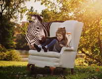 Child Reading Education Book with Animals. A young child is reading a book on a white chair with a zebra and owl next to her in nature for an education or stock photos