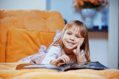 Child reading magazine on sofa Stock Photography