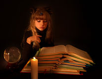 Child reading magic book at candle.