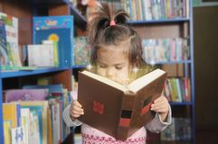 Child reading magic book. little girl in laibrary looking into fairy tale. wonder of education royalty free stock photography