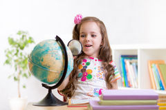 Child reading with magnifying glass look the globe Stock Photos