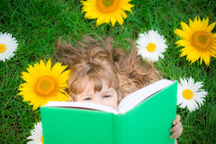Child reading in park Royalty Free Stock Photos