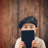 Child Reading Tech Tablet on Wood Royalty Free Stock Images