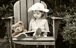 Child reading to her teddy bear Stock Images