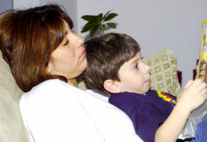 Child Reading To Mother Stock Photo