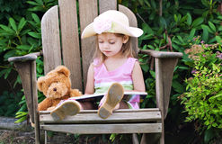 Child reading to teddy bear. Little girl pretending to read to her teddy bear Royalty Free Stock Image