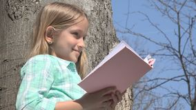 Child Reading in Tree Park, Schoolgirl Reads Book Outdoor in Nature, Educative stock images