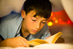 Child reading. Under the covers Royalty Free Stock Photo