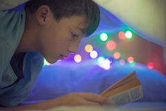 Child reading. Under the covers Stock Photo