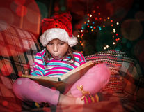 Child reads a book at Christmas. Royalty Free Stock Photography