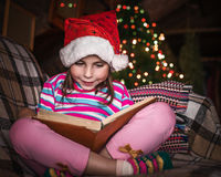 Child reads a book at Christmas. Royalty Free Stock Image