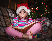 Child reads a book at Christmas. Royalty Free Stock Images