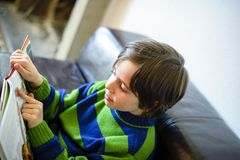 Child reads book on couch Stock Photo