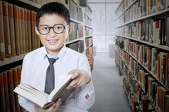 Child reads book in the library aisle. Little boy reading a book while standing in the library aisle and smiling at the camera Royalty Free Stock Photos