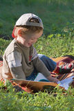 Child reads book and smiles Royalty Free Stock Image