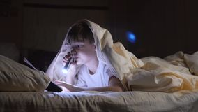 A child reads a book under blankets with a flashlight at night. Enthusiastic boy stock footage