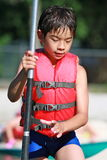 Child is ready for adventure. A 10 years old boy is getting ready for a canoe adventure Royalty Free Stock Photos