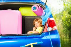Child ready for car trip. Little three years old boy sitting in the car trunk waiting for parents to put bags for the trip in the car Royalty Free Stock Photography
