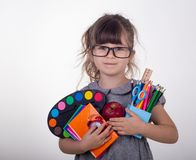 Child ready for school. Cute clever child in eyeglasses holding school supplies: pens, notebooks, scissors and apple. Back to school concept. Space for text stock photo
