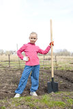 Child ready to dig. Girl in the garden with a shovel ready to dig stock photography