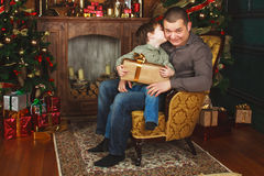 Child received a gift from his father. N Stock Photos